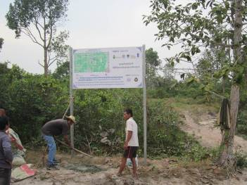 Community members set up a COMDEKS sign board at the entry to the site of a project to promote community forestry management and livelihood improvement.
