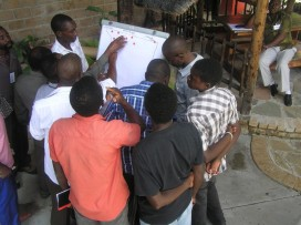 The men's group creating their map during the baseline assessment mapping activity.